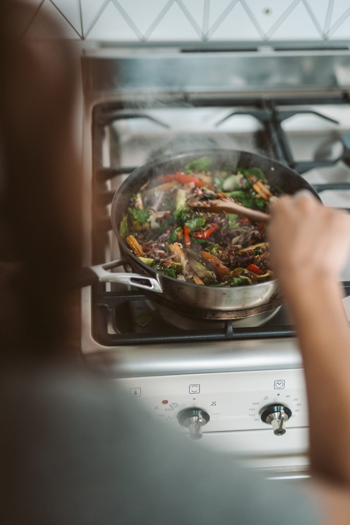 Are you an active or passive patient? Woman cooking meal on stovetop.