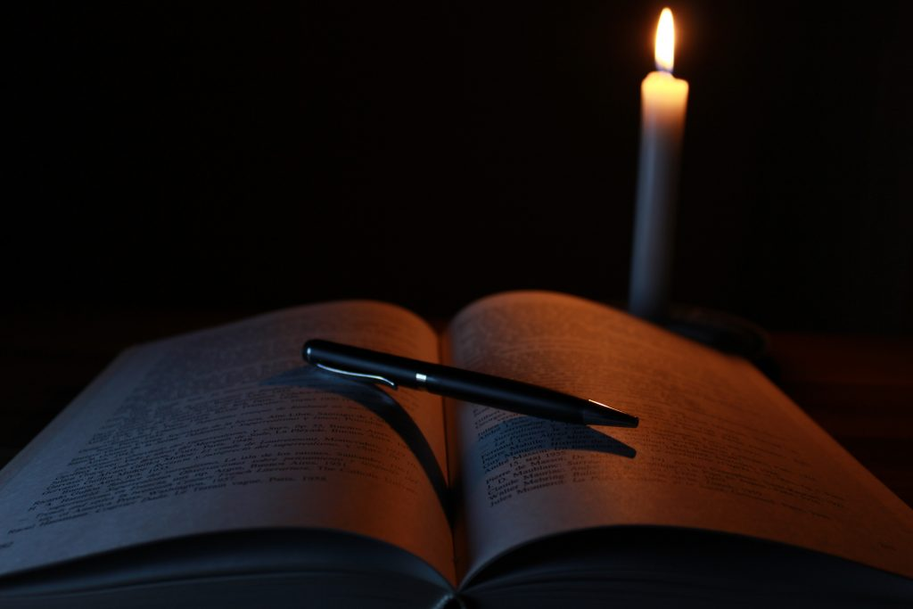 Why I Set New Moon Intentions; book, candle and pen