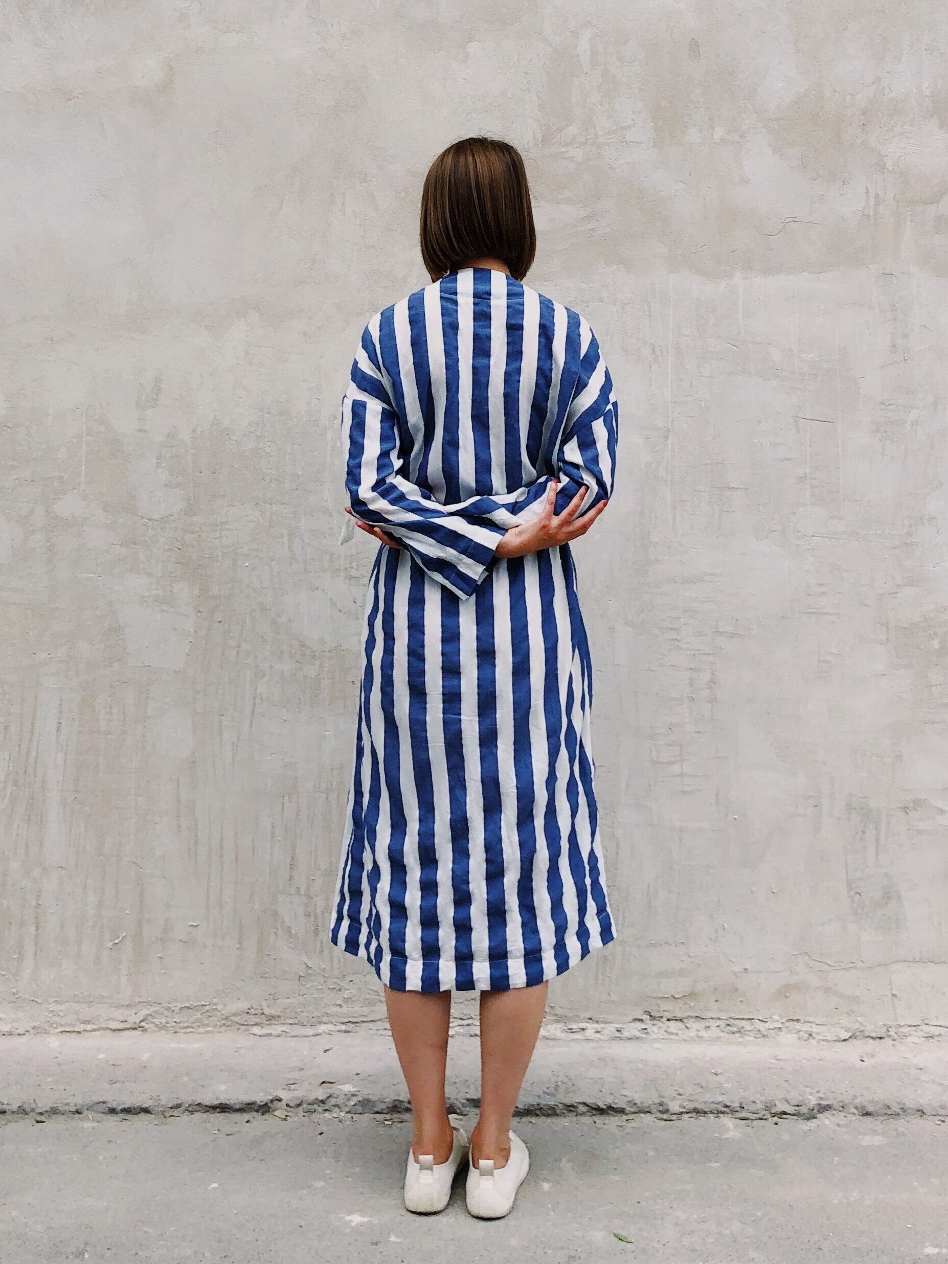 Hitting The Wall (woman in blue and white striped dress, facing away from camera towards stone/plaster wall)